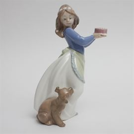 "Nao by Lladró ""Puppy's Birthday"" Figurine: A Nao by Lladró figurine. Titled ""Puppy's Birthday"", this figurine features a girl in a blue shirt, white skirt, and yellow apron, holding a cake and looking down over her shoulder at a brown puppy. The underside is stamped ""Nao Hand Made In Spain by Lladró © Daisa 1987 1045"". Written in black is ""2002""."