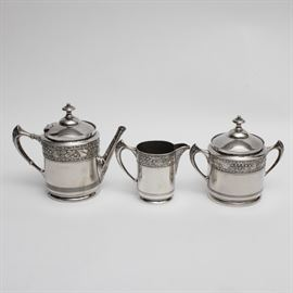 "Middletown Plate Co. Quadruple Plate Tea Service: A Middletown Plate Co. tea service. This set includes a teapot, lidded sugar bowl, and creamer in matching pattern. The underside of the teapot has a scale hallmark and reads ""Middletown Plate Co Quadruple Plate 1000 Hard White Metal 5"" and is engraved ""4912""."