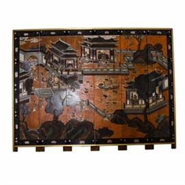 Vintage Chinese Folding Screen in Wall Frame: A vintage Chinese folding screen in a wall frame.The six panel wood screen depicts figures, buildings, trees, and a pond. The scene is bordered in black with a floral vine motif running throughout. Each of the panels is finished with two brass capped feet. The folding screen is set in a brass tone frame.