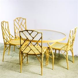 Vintage Cast Metal Bamboo Style Patio Table and Chairs: A vintage cast metal bamboo style patio table and chairs. The yellow circular table has a glass top with curved legs. The four yellow chairs have a bamboo design to back with a woven style seat and bamboo style legs. The table and chairs are unmarked.