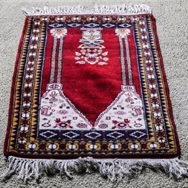 Handwoven Persian Prayer Rug: A handmade Persian prayer rug featuring a traditional mihrab, or prayer niche, with decorated columns to either side, a large, decorative vase form with a flower bouquet on a plinth, and an arch pane at the top in a contrasting white color filled with large flower blossoms seeming to ascend upward. The rug has a wide primary border on yellow with a geometric pattern, with panels to either end, and an allover palette of blue, white, and red. It has a natural wrap fringe and is unmarked.