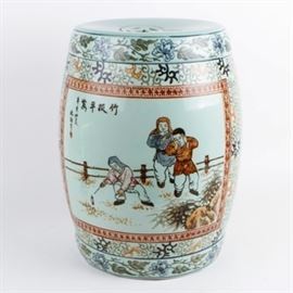 Chinese Ceramic Drum Stool: A Chinese ceramic drum stool. The stool features the image of two figures watching a third figure playing next to a wood fence. The image is surrounded by a green, black, yellow, and blue floral and foliate design. The piece is unmarked.