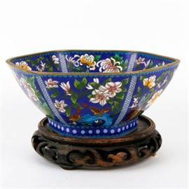 Chinese Cloisonne Bowl: A Chinese cloisonné bowl with stand. This hexagonal bowl has a gilt rim and blue body featuring a floral pattern with butterflies and birds to the interior and exterior. The piece is unmarked comes with a carved wood stand.