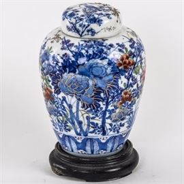 Antique Japanese Imari Ginger Jar: An antique Japanese Imari ginger jar. The lidded jar features an exterior painted with blue and red flowers with gold accents and a bird flying overhead. The piece comes with the original inner lid which contains a blue pinecone and a black circular wood base.