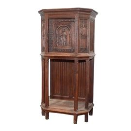 Tabernacle Style Cabinet: A tabernacle style cabinet. This wood cabinet with beveled edge and molded trim features fluted side panels and a central cabinet door with a relief carving of a man on the panel opening into a space with two shelves and gold tone hook on the interior side of the door. This piece rises on tapered legs and features an exposed bottom shelf with paneled backing. There are no visible markings or labels on this piece.