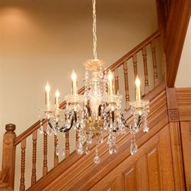 Crystal Chandelier: A crystal chandelier. The piece offers a gold tone metal frame and several crystal swags. The fixture offers twisted arms that lead to eight candle sticks with dangling crystal pendants.
