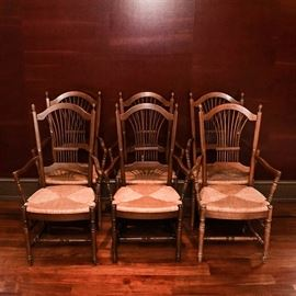Set of Six Rush Seat Oak Dining Chairs: A set of six rush seat oak dining chairs. The chairs feature walnut stained wooden bodies with arched crestrails between finial topped stiles, with fanned and gathered stiles on the back. The angled arm rests, legs, and trestle stretchers are ring and vase turned. The seats are rush woven.
