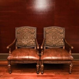 Contemporary Louis XIII Style Armchairs: A pair of matching Louis XIII style armchairs. They have walnut stained wooden frames with sloped arms and wide twist to the tapered armrest stiles and legs; the aprons and backs are accented by a serpentine pattern of carved leaves. The backs are inlaid with a tapestry style upholstery with a center palmette surrounded by acanthus leaves and vining, in warm neutral colors. The wide, padded seats have a mottled brown upholstery with leather texture and accent stitching in the center.