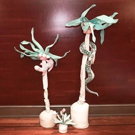 Handmade Fabric Plants and Trees: A group of handmade fabric plants and animals. Two of these pieces depict tall, tropical trees, and one depicts a blooming tropical plant, all in cloth planters. One tree has a cloth snake coiled around the trunk, and one has a lizard in the leaves.