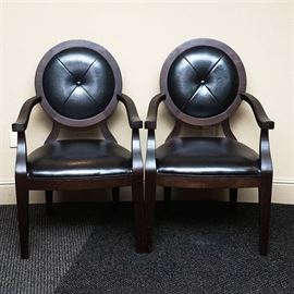 Oval Back Leather Armchairs: A pair of matching wood and leather armchairs. They have dark stained wooden frames, with circular backs, sloped armrests, and tapered block feet. The backs and trapezoid seats are padded and upholstered in black leather, and the backs have a button accent in the center of four triangular panels.