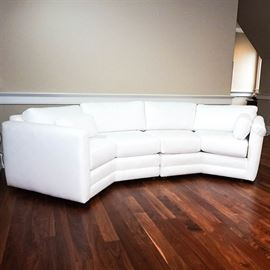 White Sectional Sofa by Norwalk Furniture: A white sectional sofa by Norwalk Furniture. It has two sections, each with a side armrest and two seats, angled in the center. The armrests sit even with the back, and it has back and seat cushions, as well as matching throw pillows. It is upholstered in white fabric and sits on recessed wooden feet.