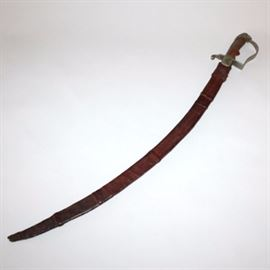"""Late 19th Century Ethiopian Cavalry Saber: An Ethiopian cavalry saber with tooled leather scabbard from the reign of Menelik II (1844-1913), who was in power from 1889-1913. It features a stirrup form, nickel-plated brass hilt, uncovered wooden grip, and lion's head pommel. The single-edge, fullered blade has been etched with foliate designs. The ricasso bears a Lion of Judah to one side and Ge'ez inscription above """"T. M."""" with profile of Menelik II to the verso. The curved blade is approximately 32.5"""" (83 cm) long. The handmade scabbard has been etched with a variety of designs, including the Arabic star and crescent, and bears the names Akamed Hussein and Mohamed Hussein. Menelik II was in conflict with Italians who were trying to expand their territory."""