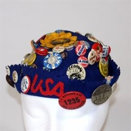 Vintage Felt Beanie with Pinbacks: A vintage felt beanie with numerous pinbacks and lapel pins from the 1930s and 1940s. The letters USA are applied to the beanie's brim. Included are pinbacks depicting Hollywood stars of the day, political pins touting Langdon and Knox, Stevenson, Ike, Bob Taft and more, as well as union buttons and much more!
