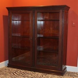 Antique Mahogany Bookcase: An antique mahogany bookcase. The piece features two glass front doors, wood knobs, and three adjustable shelves. It is adorned with both carved and applied dental molding, and flanked by ionic columnar details.