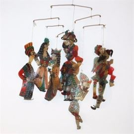 Vintage Persian Shadow Puppet Mobile: An animated mobile comprised of vintage Persian-Acem shadow puppets. This unique piece features silhouettes of four men and four women, with reticulated limbs. The puppets are individually affixed with a delicate string to copper wire extensions that fall from a single grasp. The elements are created from hand painted, opaque hide material.