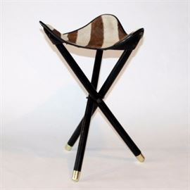Vintage Zebra Hide Stool: A vintage zebra hide collapsible stool. The piece features a triangular seat made of zebra hide with three leather pockets for stool's legs. The collapsible tripod-like stand is constructed of wood rods that are painted black with brass cleats.