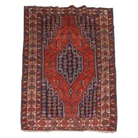 Hand-Woven Turkish Area Rug: A vibrantly colored, hand-woven Turkish area rug. The handmade wool rug features a dark blue geometric diamond in the center, with flowers, in colors of red, white, green and blue. This center diamond is framed by a wide, red geometric border, featuring vines of geometric shapes and flowers. The spandrel corners have dark blue backgrounds that match the center diamond. The center panel is framed by three outer borders. The guard border is unresolved, featuring a red crab motif on a white background. Both of the flanking borders have a red background, with small flowers. The rug has a hand-overcast edge, and natural warp fringe. No maker's marks or labels.