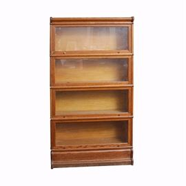 """Barrister's Bookcase: A vintage oak barrister's bookcase, with glass front doors. The bookcase is made of medium stained oak with plywood backing, and the sides and corners are wrapped with copper tone metal strips. The cabinet features four compartments, each with its own sliding glass door. The doors lift up from the bottom and slide inside on tracks. The bookcase cabinet rests on a molded base, and is marked """"Elastic Bookcase"""" to the top center, and also to the back of the interior. This item matches item 17DEN019-111."""