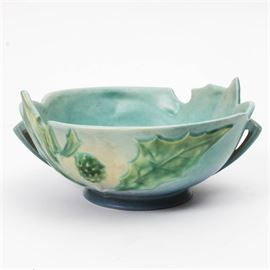 """Roseville """"Thornapple"""" Pottery Bowl: A vintage Roseville pottery bowl in the Thornapple pattern. The hand-painted pottery bowl is glazed in satin matte aqua and periwinkle blue. It features raised designs of leaves and berries on one side, with a flower on the other side. The bowl is marked to the underside """"Roseville 309-8""""."""