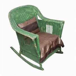 """Vintage Wood and Wicker Rocking Chair: A vintage wood and wicker rocking chair. The woven wicker chair has wide, flat arms and a curved back with a woven diamond pattern. The chair has straight, round legs that rest on wood rockers. The entire chair has been painted green. It comes with a modern seat cushion and throw pillow in a shiny brown and tan striped fabric, which are labeled """"Classic Home"""" by Target."""