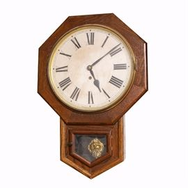 Antique Waterbury Drop Octagon Oak Clock: An antique Waterbury drop octagon oak wall clock. The clock features an octagonal frame around the dial, which is white enameled steel. The clock dial features black Roman numerals and hands, and has a brass bezel around the crystal. Below is an arrow-shaped cabinet housing an ornate brass tone pendulum. A small brass knob is affixed to the hinged door to access it.