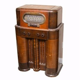 """Vintage RCA Victor Radio Cabinet: A vintage RCA Victor tube radio cabinet. The heavy, circa 1940s or '50s wood radio cabinet has rounded edges and sides, with contrasting veneered woods applied to different areas of the cabinet, and brown Bakelite buttons and knobs. There is a large oval dial on the front, marked with various settings, including """"Short Wave"""", """"Police"""", """"Amateur"""", and others. The rectangular buttons on the front are marked with various radio stations. The dial is marked """"Standard Domestic"""", with """"RCA Victor"""" marked to a plate mounted just above it. A decal label on the front is marked """"Designed for Television Attachment""""."""