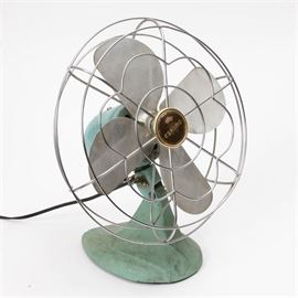 """Vintage Eskimo Table Fan: A vintage Eskimo brand table fan. The electric fan is marked """"Eskimo"""" and """"Model 1005R"""" to the center of the blade hub. It has four silver tone metal blades within a silver tone wire cage. The base and motor have a light turquoise blue painted finish. The neck of the base can be adjusted to aim the fan as desired."""