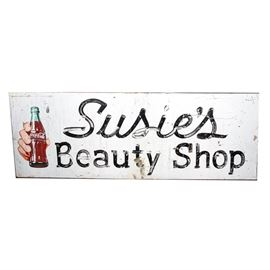 """Coca-Cola Beauty Shop Sign: A vintage Coca-Cola sign. This sign features a metal construction and is painted white. The sign indicates """"Susie's Beauty Shop"""" in black letters with a disembodied hand holding a bottle of Coca-Cola on the left side."""