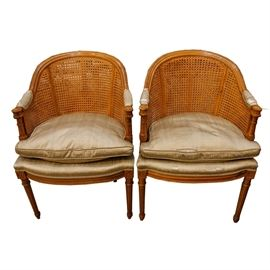 Pair of Vintage Louis XV Style Caned Bergère Chairs: A pair of vintage Louis XV style caned Bergère chairs. This pair have walnut finishes with champagne colored upholstery to the armrests and seats. The rounded backs are caned, with carved floral detail on the hand rests above the turned arm supports. The chairs rise on fluted legs with carved floral top blocks.