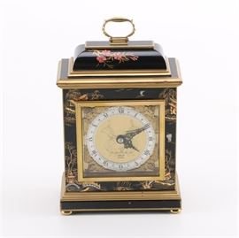 """Elliot of London Mantle Clock: An Elliott of London mantle clock. This piece features a black lacquered body with Asian inspired motif to each side. The gilded face is set with a band of white for the time compass mechanisms and numbering. Marked """"Made in England""""."""