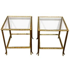 Pair of Regency Style Iron End Tables: A pair of Regency style iron end tables. This pair are square with glass tops. The tops are framed in gold-toned painted iron. The bases are formed by four gold-toned painted legs, with each leg splitting into two splayed feet. Each table has a lower glass shelf.