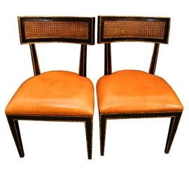 Mid Century Modern Leather Side Chairs: A pair of Mid Century Modern leather side chairs. The chairs are wood with a chestnut finish and feature a curved rectangular back with a caned splat. Other features include square wood supports, a light brown leather seat, carved one piece apron and tapered legs.
