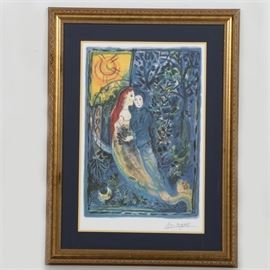 """After Marc Chagall Limited Edition Offset Lithograph """"The Wedding"""": A limited edition offset lithograph on paper of an original painting by Marc Chagall (1887-1985) titled The Wedding. This colorful abstract print depicts a couple embracing in a landscape filled with a variety of plants. The print is numbered 287 in an edition of 500 to the lower left and features a printed signature to the lower right margin. Mounted under a double layer of yellow and navy matting, the print is presented under glass in a gold tone wood frame. Hanging wire and a Certificate of Authenticity are present to the verso of the frame. Known for his contributions to the Cubism, Symbolism and Fauvism movements, Chagall is best known for his abstract paintings and public art."""