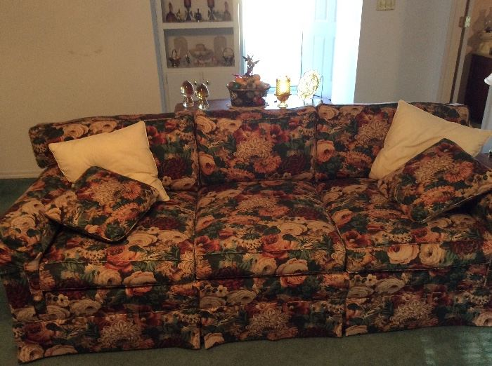 Sofa with sofa table behind it - collectible items on sofa table and built in bookshelf with additional collectibles.