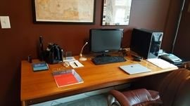 wooden desk, computer, leather chair, framed map