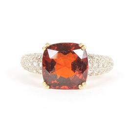 Garnet and Diamond 18K Gold Ring: An 18K yellow gold ring, featuring a cushion cut natural pyrope garnet basket set above diamond encrusted shoulders.