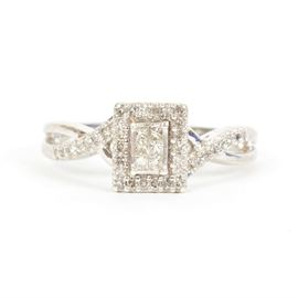Silver and Diamond Ring: A sterling silver ring, featuring six princess cut diamonds illusion set into a center rectangle and surrounded by a rectangular halo of diamonds, all raised on a basket setting with a double curl detail to the gallery. The shoulders feature an open twist, each with the top arm of the twist set with diamonds.