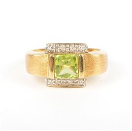 18K Matte Yellow Gold Peridot and Diamond Ring: An 18K matte yellow gold peridot and diamond ring. This cocktail ring features squared shoulders and a princess cut peridot with diamond accents.