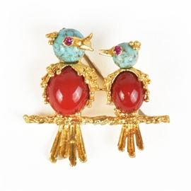 18K Yellow Gold Bird Brooch: An 18K yellow gold bird brooch. This yellow gold brooch features two bird figurines with blue and red glass accents, gold feathers and synthetic ruby eyes on a gold branch.