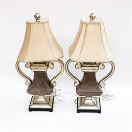 Matching Trophy Shape Accent Lamps: A pair of accent desk lamps. These pieces feature composite frames that are gold and silver in tone in the shape of trophies. Each lamp comes with an octagonal empire style shade that is cream in tone.
