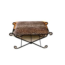 Animal Print Bench by Trend Setting Designs: An animal print bench by Trend Setting Designs. This piece features a square seat with leopard print pattern on a black metal frame featuring scrolling edges and floral ornamentation at the crossing legs terminating on scrolling feet. This item is marked with a manufacturer's tag on the underside.