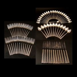 "International Silver Co. Sterling ""Golden Tradewinds"" Flatware: A collection of International Silver Co. sterling silver flatware in the Golden Tradewinds pattern. This set includes eleven dinner forks, twelve salad forks, twelve iced tea spoons, twenty-two teaspoons, one sugar spoon, and twelve hollow handle knives with stainless blades. These pieces feature pierced handles with the woven Golden Tradewinds pattern. They are all marked ""International Sterling""."
