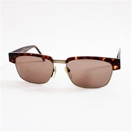 """Lafont Paris sunglasses: A pair of Aloyon A35 sunglasses from the company Lafont. This pair features tinted lenses that are soft violet in tone. The lenses are held in composite frames that are dark tiger's eye in tone with text presented in white. The text """"Jean Lafont Paris Frame France"""" appears on the right arm and """"Aloyon A35"""" on the left one."""