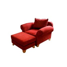 Upholstered Armchair With Ottoman: An upholstered armchair with ottoman. This piece is upholstered with a red fabric and features a round back with curved armrests and oversized pillow cushion back and removable seat cushion terminating on tapered feet. Also includes a red ottoman with cushion top terminating on tapered feet. There are no visible marks or labels on these pieces.  See item 17HOU012-032 for matching piece.
