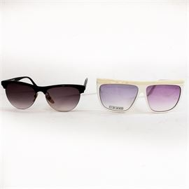 """Vintage Oleg Cassini and Liz Claiborne Sunglasses: A pair of vintage sunglasses. This pairing contains a pair of sunglasses from Liz Caliborne and Oleg Cassini respectively. The Caliborne sunglasses have dark violet tinted lenses attached to jet black frames and amber nose rests; with the text """"Liz Claiborne"""" on the right arm and """"LC 26 BLK 145"""" on the left arm. The Oleg Cassini sunglasses have light violet tinted lenses that are attached to bone white frames with a scaled textured top and the text """"Oleg Cassini-911 584"""" on the right arm and """"63-13 140mm"""" on the left arm. The lens quality sticker is still present on the Oleg Cassini sunglasses."""