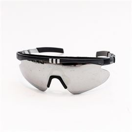 Adidas 9509 Sport Visor Sunglasses: A pair of 9509 sport's visor sunglasses from the company Adidas. The lens on this piece is in the shape of a visor and is supported on a hard plastic frame that is black and chrome in tone. The identification markings are placed above the visor that protects the user's right eye.