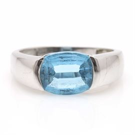 18K White Gold Topaz Ring: An 18K white gold topaz ring. This ring features a smooth shank leading to a half bezel set blue topaz stone.