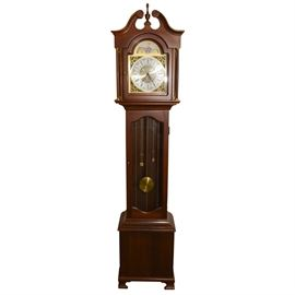 "Daneker Grandfather Clock: A grandfather clock by Daneker. This clock is made of a dark mahogany with gold tone accents and features a broken arch pediment and finial. The clock has an ornate gold tone face with the quote "" Lord, through this hour be Thou our guide"" with black Roman numerals with filigree accents under a matching moon dial. A side door offers access to clock's works. The front glass displays a gold-tone pendulum and lyre with levers."