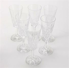 "Waterford Crystal ""Lismore"" Glasses: A selection of six Waterford Lismore glasses. Each glass has geometric and diamond designs along the bottom of the cup that sits on a faceted stem and circular base that has a sunburst design to the bottom of it. There is a Waterford mark to the base of each cup."