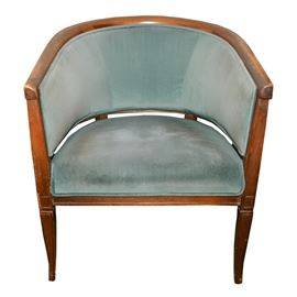 Empire Style Barrel Chair: An empire style barrel chair. The chair is wood with a mahogany finish and features a curved wood top rail, wood back supports and upholstered sides and seat, corner blocks and tapered legs. The chair has a light blue velvet cloth with cloth piping.